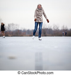 Young woman ice skating outdoors on a pond