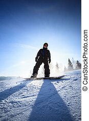 Young man snowboarding down a slope on a lovely sunny winter...