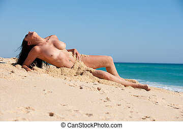 Brunette woman at the beach lying in the sand - Beautiful...