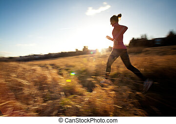 Young woman running outdoors on a lovely sunny winter/fall...