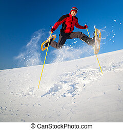 Young man having fun while snowshoeing outdoors on a lovely...