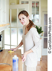 Young woman doing housework, cleaning the kitchen