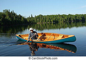 Paddling a canvas cedar canoe - Canoeist paddling a cedar...