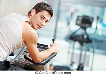 positive man at legs bicycle exercises machine - smiling...