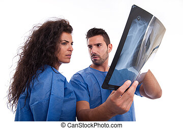 Medical staff looking at x-ray - Two doctors loonking and...