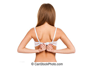 young woman taking off her bra - Rear view of a young woman...