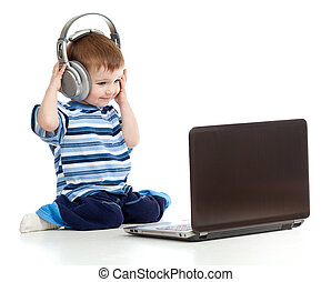 Funny child playing with laptop and listening to music in...