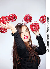 woman holding red balls