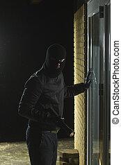 Burglar holding flash light