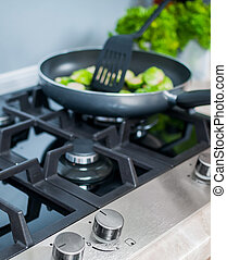 gas-stove with vegetables dish prepared in a black skillet...