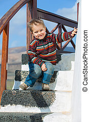 Happy little boy sitting on stairs in the background of blue...
