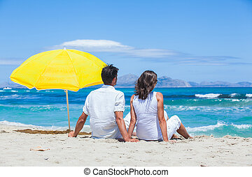 Couple sitting together on the beach and looking out at...