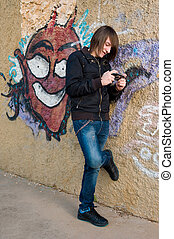 Urban scene - Teen playing with a console in a grunge urban...
