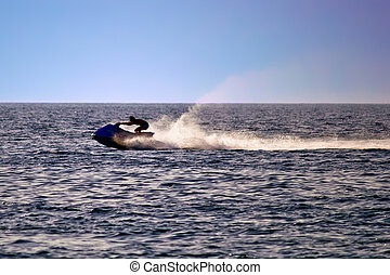 Man on jet ski silhouette, sea at late afternoon