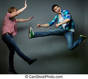 Tricky jump - Guy jumping into air and kicking his friend,...