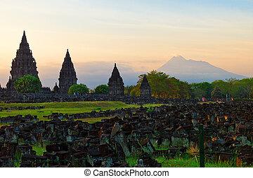 Prambanan hindu temple in Yogyakarta with Merapi volcano on the background