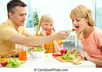 Try this - Family eating fresh vegetables, man giving his...