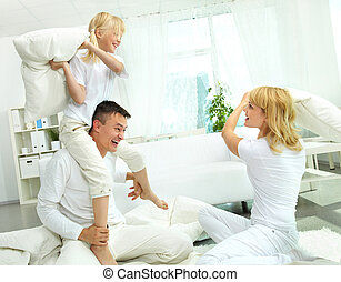 Family pillow fight - Cheerful family having a lot of fun...