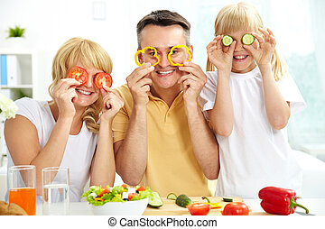 Playful family - Cheerful family playing with vegetables in...