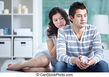 Troubled couple - Unhappy lovers sitting together indoors