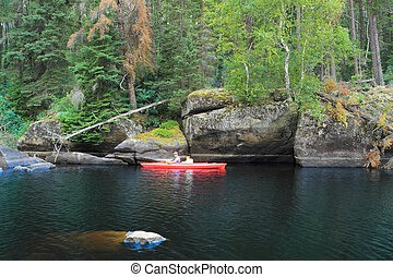 Family canoeing in a beautiful remote lake