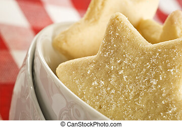 Sugar coated shortbread cookies in star shapes stacked up -...