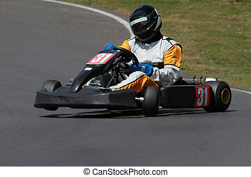 Racing go kart with front wheel in the air as he is going...