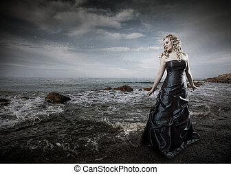 Woman in dress at ocean
