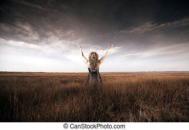 Woman lifting her hands up in a field - Blonde woman with...
