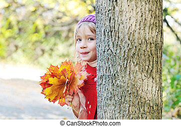 Peekaboo - little girl with leaves in forest - Peekaboo! I...