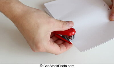 Red stapler secures a sheet of pape
