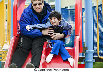 Father going down slide with disabled son who has cerebral...