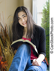 Beautiful teenage girl studying next to sunny window -...