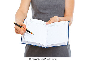 Closeup on pen pointing in open notepad in hands of female