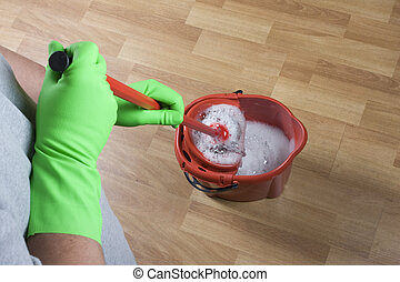 mopping - cleaner is mopping wooden parquet floor