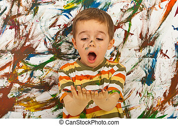 Amazed child looking at messy palms - Surprised child boy...