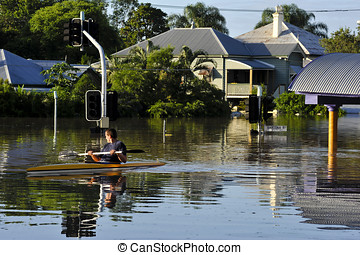 flooded streets - a man uses a canoe to traverse the flooded...