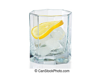 Glass with ice and slice of fresh lemon on a white...
