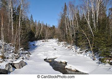 Frozen River - Partially frozen river winding through a...