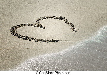 Heart on sand with wave approaching - Handwritten heart on...