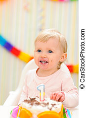 Portrait of eat smeared baby with birthday cake