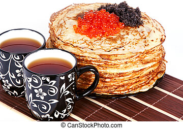 Tea and a pancakes with caviar - Cups with tea and a pile of...