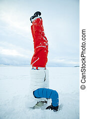 Headstand in winter - Woman doing yoga and a headstand in...
