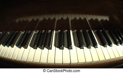 Piano keys dolly fish above - A dim lit dolly shot of piano...