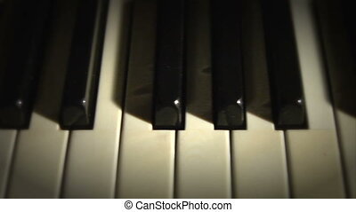 Piano keys dolly cu above2 - A dim lit shot of piano keys...