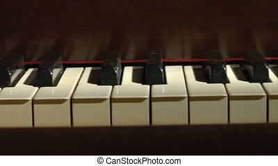 Piano keys dolly cu - A dim-lit dolly shot of piano keys...