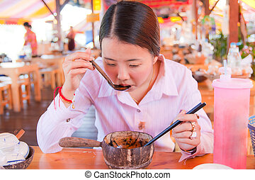 Asian woman eating noodle in the restaurant