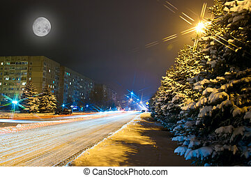 Night snowy road in the small town