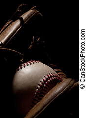 Macro Baseball and Glove on Black Background - Macro shot of...