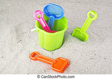 Child's bucket, spade and other toys on beach